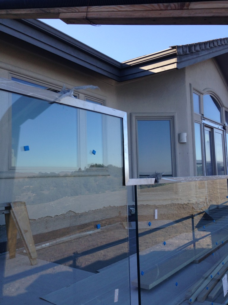 """Photos during installation of 9/16"""" Tempered Laminated Deck Railing with Custom Welded Stainless Steel Cap"""
