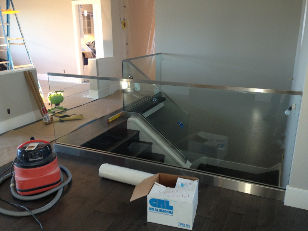 Interior Stairwell Glass Guardrail at landing and custom stainless steel cladding