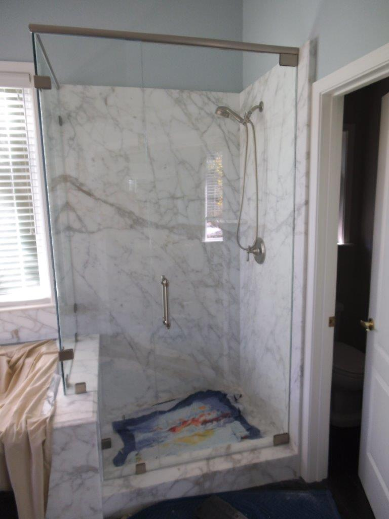 "Frameless Shower Door with a Brushed Nickel Shower Door Header.  Pivot Hinges and 3/8"" Tempered Glass Door"