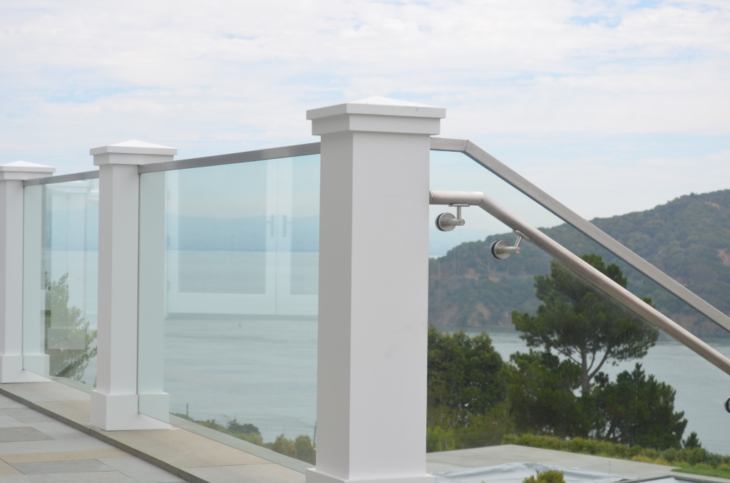 "1/2"" Glass Deck Railing Between Wood Posts.  A frameless base shoe system is used going down the stairs."