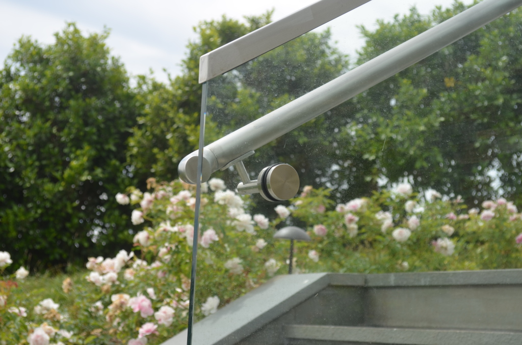 Glass handrail bracket in brushed stainless steel.