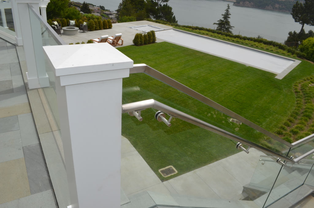 Detailed view of glass railing with handrail and handrail brackets.
