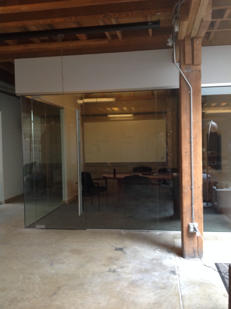 "Glass Conference Room constructed using 1/2"" clear tempered glass.  Hardware is satin anodized with a ladder pull."