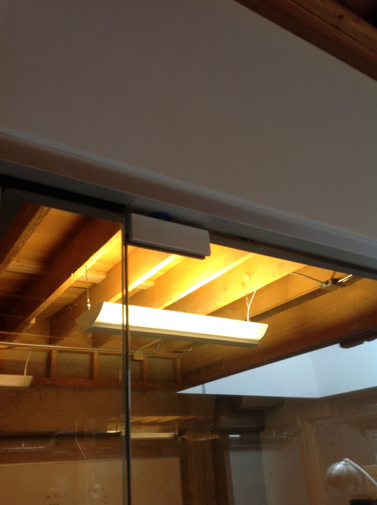 Patch fitting used to attach the glass to the overhead concealed ADA closer.